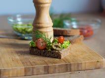 Pão orgânico com abacate e tomates na placa de madeira Imagens de Stock