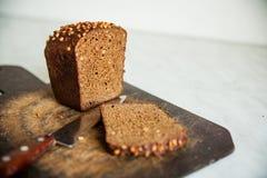 pão preto com as sementes de girassol na placa de corte Fotos de Stock
