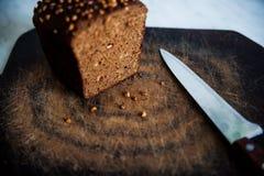 pão preto com as sementes de girassol na placa de corte Fotografia de Stock Royalty Free