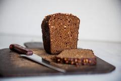pão preto com as sementes de girassol na placa de corte Foto de Stock Royalty Free