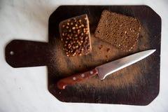 pão preto com as sementes de girassol na placa de corte Imagens de Stock Royalty Free