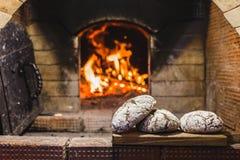 Pão recentemente cozido delicioso no fundo o forno e os carvões no fogo foto de stock royalty free
