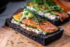 Pão Salmon Sandwiches fumado do carvão vegetal na placa de madeira Imagem de Stock