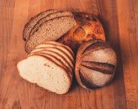 Pão sortido do branco e de centeio em uma tabela de madeira Vista superior Pão cortado friável perfumado fresco O naco do branco  Foto de Stock