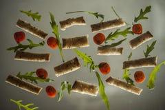 Pão torrado, rúcula e tomates em um fundo claro Fotografia de Stock Royalty Free