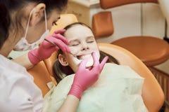 Pädiatrische Zahnheilkunde Zahnarzt behandelt Zähne wenigen Mädchens lizenzfreie stockbilder