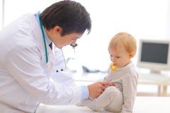 Pädiatrischer Doktor, der das Schätzchen verwendet Stethoskop überprüft lizenzfreie stockbilder