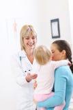 Pädiatrischer Doktor, der mit Mutter und Schätzchen spricht Lizenzfreies Stockfoto