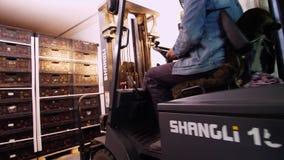 Päfyllning av en lastbil en arbetare på en liten auto-laddare, elektriska gaffeltruckimporter, laddar askar av äpplen in i ett st lager videofilmer