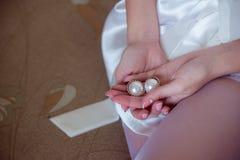 Pärlemorfärg örhängen i händerna av bruden Royaltyfri Foto