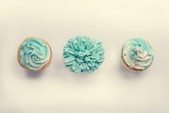 Pärlemorfärg födelsedagmuffin med smörkrämisläggning Arkivbild