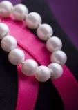 Pärlemorfärg halsband över rosa band fotografering för bildbyråer