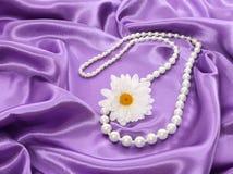 Pärlemorfärg halsband med chamomileblomman på violett silk tyg Royaltyfri Foto
