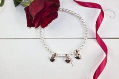 Pärlemorfärg halsband med guld- hjärtor på vitt trä Royaltyfria Foton