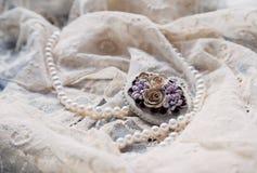 Pärlemorfärg halsband- och antikvitetbrooche snör åt på Arkivfoton