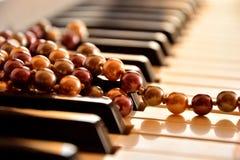 Pärlemorfärg halsband på pianotangentbordet Royaltyfri Bild