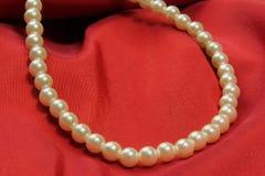 Pärlemorfärg halsband på rött tyg Royaltyfri Bild