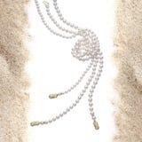 Pärlemorfärg halsband på sand Royaltyfri Foto