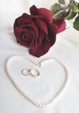 Pärlemorfärg hjärta, en ros och vigselringar Arkivfoton