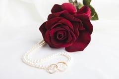 Pärlemorfärg hjärta, en ros och vigselringar Arkivbild