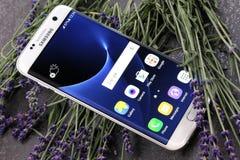 Pärlemorfärg Samsung S7 KANT på en lavendelbakgrund Royaltyfri Foto