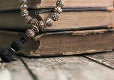 Pärlor som ligger på den sjaskiga slog gamla boken som ligger på det gamla sprucket royaltyfria foton