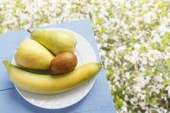 Päron, banan och kiwi på träblåtttabellen och på naturlig blommabakgrund organiska nya frukter Top beskådar kopiera avstånd Royaltyfri Foto