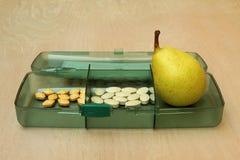Päron i en packe av vitaminer Arkivbilder