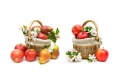 Päron och äpplen i en korgcloseup på en vit bakgrund Arkivbild