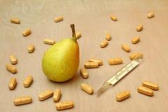 Päron och läkarundersökningtermometer Arkivfoton