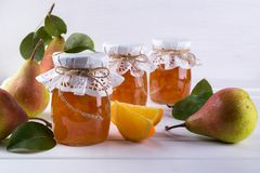 Päron och orange driftstopp i exponeringsglaskrus med mogna päron, kanelbruna pinnar, anisstjärnor och gräsplansidor på tabellen Royaltyfri Fotografi