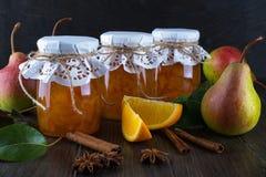 Päron och orange driftstopp i exponeringsglaskrus med mogna päron, kanelbruna pinnar, anisstjärnor och gräsplansidor på tabellen Royaltyfri Bild
