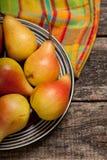Päron på maträtten och torkduk på den gamla wood täckningen Arkivfoton