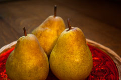 Päron på röd maträtt Fotografering för Bildbyråer