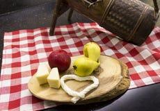 Päron, röd plommon och ostar på träskärbräda Arkivbilder