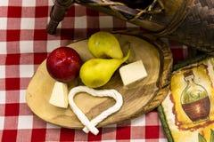 Päron, röd plommon och ostar på träskärbräda Royaltyfri Bild