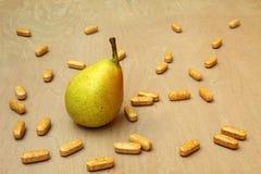 Päron som omges av vitaminpreventivpillerar Arkivbild