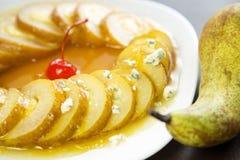 Päronstycken i orange sirap med Dorblu ost i en vit platta Royaltyfria Foton