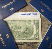 4 Pässe, 2 Dollar und Bordkarte auf hölzernem Hintergrund, Familienreisekonzept Lizenzfreie Stockbilder