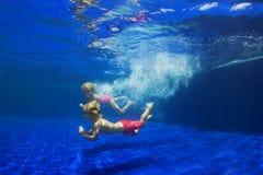 Płetwiści dzieciaki nurkują podwodnego w basenie zdjęcia stock