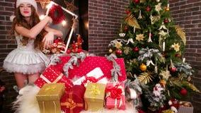 På överraskning för helgdagsafton för ` s för nytt år från Santa Claus nära julgranen grundar den lyckliga flickan för A gåvor, u arkivfilmer