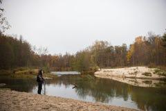 På banksjön Lockig flicka som framme poserar av sjön arkivfoto