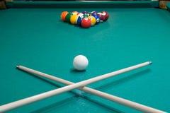 på billiardtabellen är två stickrepliker som korsas mot bakgrunden av att spela bollar arkivbilder