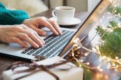På bokstäver som hänger julklockor Kvinna som skriver på bärbara datorn i hemmiljö Xmas-begrepp Hyvla ferier Röd text med loupen  fotografering för bildbyråer