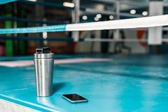 På boxningsringen finns det termos med vatten, och en smartphone är bredvid den royaltyfria bilder
