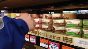 På burk mat för manköpandekatt på det Tisol husdjurlagret stock video