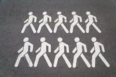På de gråa asfaltsymbolerna med bilden av att gå manvit royaltyfri foto