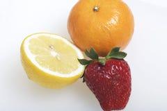På de tabelllögnfrukterna och bären: jordgubbar, citron och Mandarine Fotografering för Bildbyråer