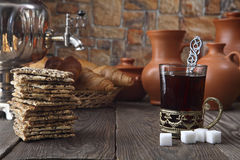 På den äta middag tabellen var: en samovar, ett exponeringsglas med te i en bronskopp-hållare, nya rullar, kakor och gammal keram Arkivbild