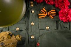 På den militära likformign är det St George bandet i formen av en pilbåge, en hjälm, en bukett av nejlikor och en flaska för vatt royaltyfri bild